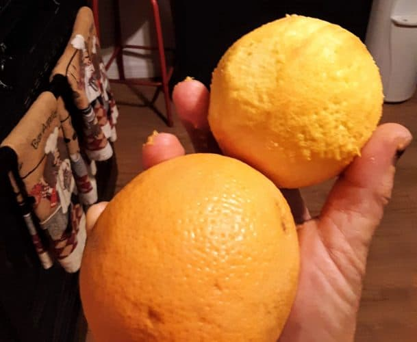 An orange that has been zasted and one that has not