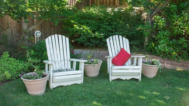 2 white adirondak chairs in the grass