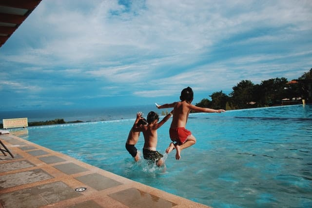 2 boys jumping in the swimming pool
