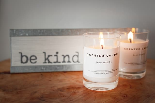s jar candles and a be kind sign on table