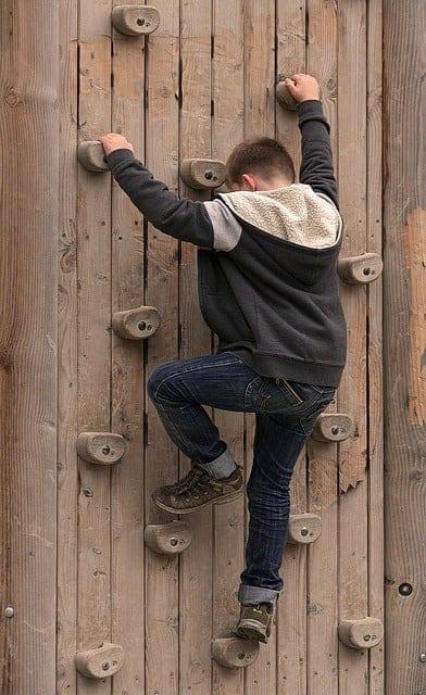 little boy climbing up a climbing wall