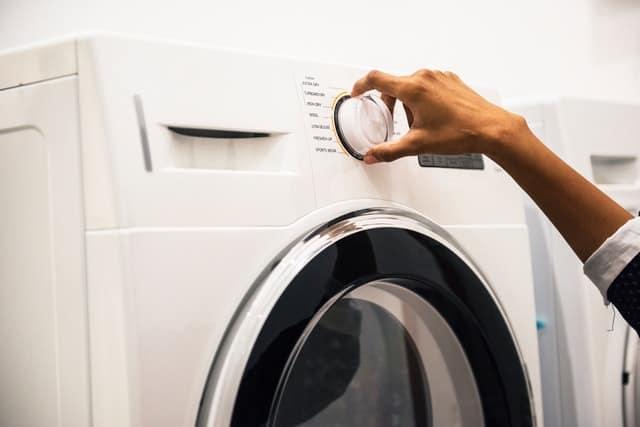 close up of someone starting a washing machine