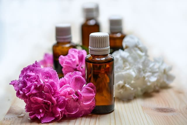 essential oils and a purple flower used for aromatherapy