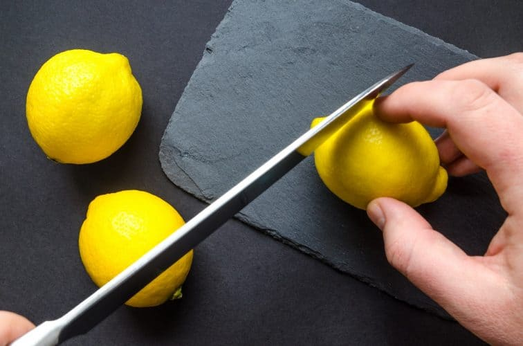 slicing lemons on a clear cutting board is a great eco-friendly cleaning idea.