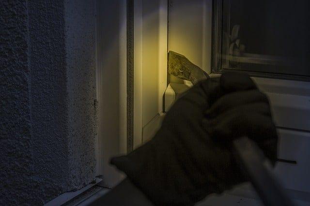 burglar prying window open with bar at night.