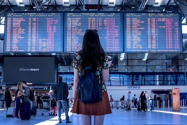 Woman at airport looking at departure screens.