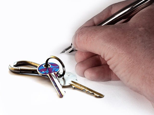 Hand holding pen and keys on the table