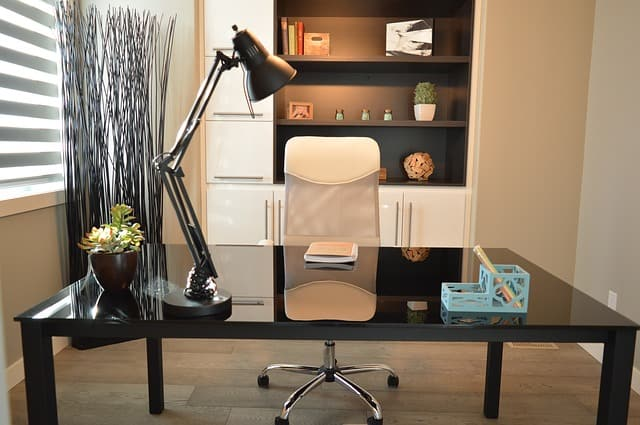 A home office with a desk and a bookshelf.