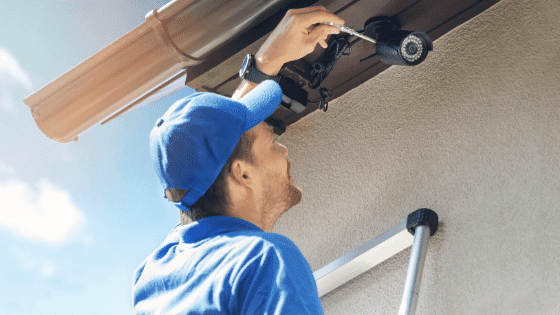 A Man installing a security camera