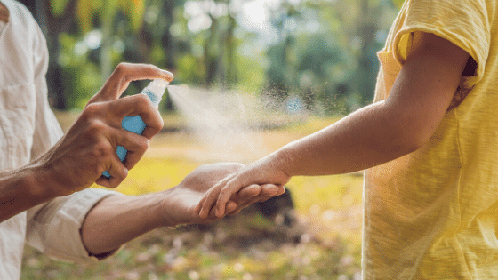 spraying mosquito repellant