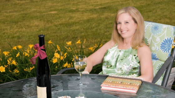 A woman with a glass of wine and a book