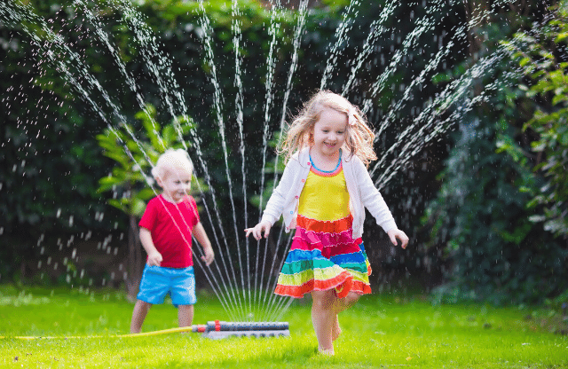 kids playing in sprinkler to beat the heat.