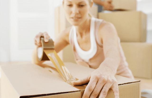 Woman taping a box.