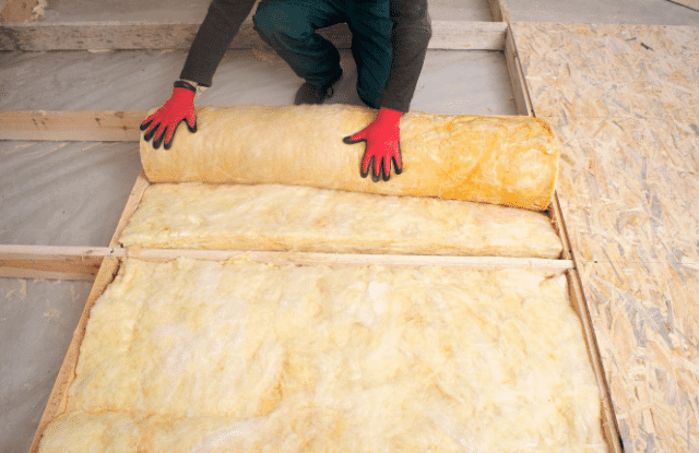 Person rolling out insulation in an attic