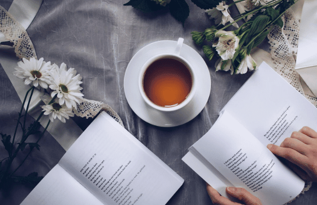 Woman with a cup of tea reading to learn.