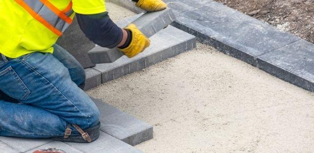 Man laying new patio pavers