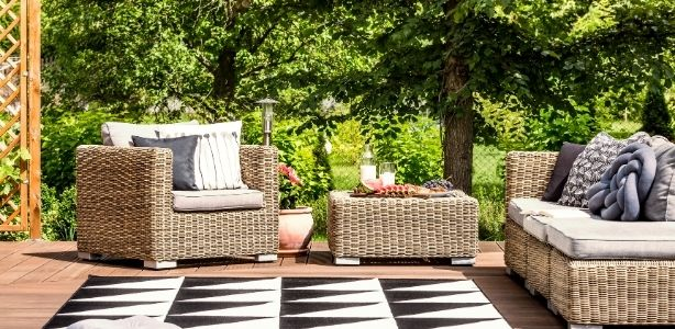 Patio with wicker furniture and an outdoor rug.