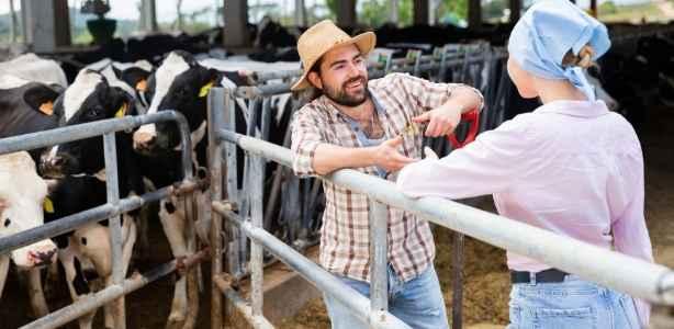 Man mentoring woman on a farm