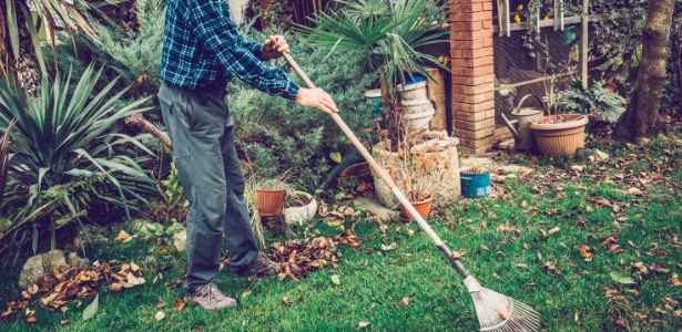 Man raking up yard after the winter season has passed