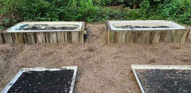Old privacy panel cut-offs around a tub in the herb garden