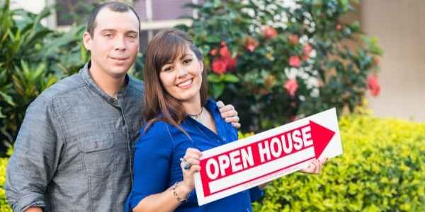 Couple holding an open house sign