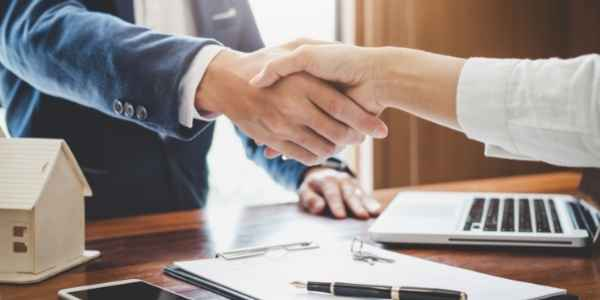 signing papers with a real estate agent
