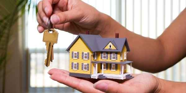 house in one hand and key in the other