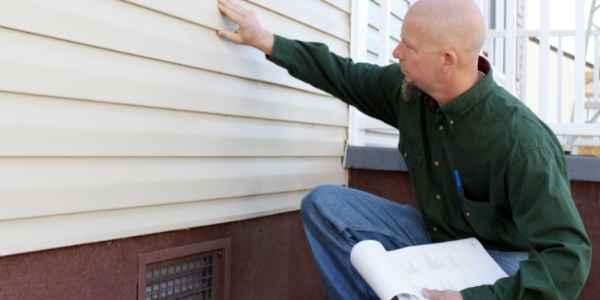Man inspecting the siding