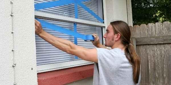 man taping windows to prevent breakage