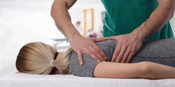 Chiropractor adjusting womans shoulder